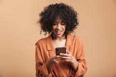 Mujer africana bonita sonriente que escribe el mensaje en smartphone fotografía de archivo libre de regalías