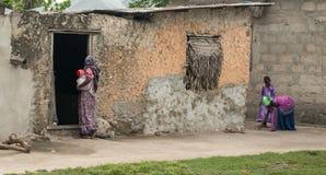 Mujer africana con el bebé en sus manos cerca de la casa vieja Imagen de archivo