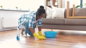 Mujer africana con el piso de la limpieza de la esponja en casa almacen de metraje de vídeo