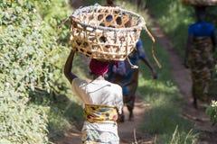 Mujer africana con la cesta en la cabeza que camina en un camino rural fotos de archivo