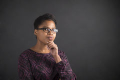Mujer africana con la mano en la barbilla que piensa en fondo de la pizarra Foto de archivo