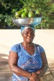 Mujer africana con la pelvis en su cabeza con los aguacates verdes maduros fotos de archivo libres de regalías