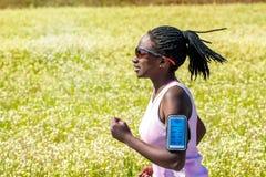 Mujer africana con las trenzas que siguen el funcionamiento en el teléfono elegante Imagenes de archivo