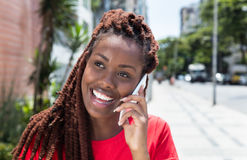 Mujer africana con los dreadlocks que se ríe del teléfono en la ciudad Fotografía de archivo