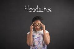 Mujer africana con los fingeres en los templos con un dolor de cabeza en fondo de la pizarra Fotos de archivo