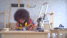 Mujer africana con los trabajos de un carpintero afro del peinado sobre la madera en el taller almacen de metraje de vídeo
