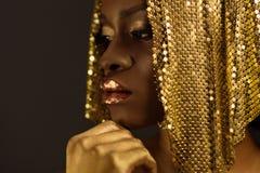 Mujer africana con maquillaje metálico del oro y labios brillantes llenos que parecen ausentes deteniendo la barbilla, cierre imagenes de archivo