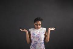 Mujer africana con no conozco gesto en fondo de la pizarra Fotos de archivo libres de regalías