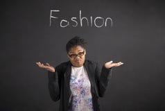 Mujer africana con no sé sobre gesto de la moda en fondo de la pizarra Foto de archivo