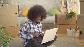 Mujer africana con un peinado afro que se sienta en el piso y que usa un ordenador portátil, concepto de mudanza metrajes