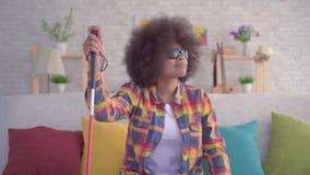 Mujer africana con una persona con deficiencias visuales afro del peinado en vidrios con un bastón en sus manos que se sientan en almacen de video