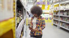 Mujer africana del ladrón con un peinado afro en el supermercado almacen de metraje de vídeo