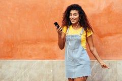 Mujer africana del norte feliz que escucha la m?sica con los auriculares fotos de archivo
