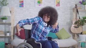 Mujer africana discapacitada alegre con un baile afro del peinado que se sienta en una silla de ruedas MES lento almacen de metraje de vídeo