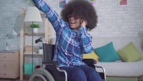 Mujer africana discapacitada alegre con un peinado afro en una silla de ruedas en auriculares que escucha la música y que canta almacen de video