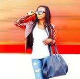 Mujer africana elegante con el bolso en ciudad sobre rojo fotografía de archivo libre de regalías