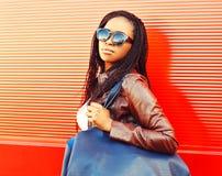 Mujer africana elegante en gafas de sol con el bolso que camina en la ciudad imagenes de archivo