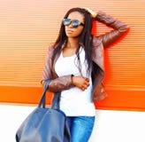 Mujer africana elegante en gafas de sol con el bolso que presenta en la ciudad foto de archivo