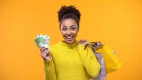 Mujer africana emocionada con los bolsos de compras que llevan a cabo las cuentas euro, venta estacional fotos de archivo libres de regalías
