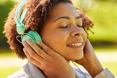 Mujer africana en auriculares que escucha la música Imagen de archivo libre de regalías