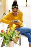 Mujer africana en banco usando el teléfono celular Fotos de archivo