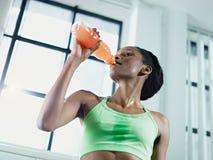 Mujer africana en bebida de consumición de la energía de la gimnasia Imágenes de archivo libres de regalías