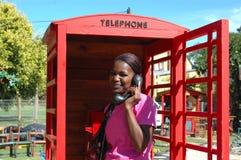 Mujer africana en cabina de teléfonos Imagen de archivo