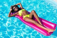 Mujer africana en el colchón de aire en piscina Imágenes de archivo libres de regalías