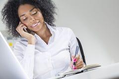 Mujer africana en su teléfono en la oficina con el ordenador portátil Fotos de archivo