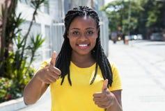 Mujer africana en una camisa amarilla en la ciudad que muestra el pulgar Foto de archivo