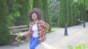 Mujer africana feliz alegre con un peinado afro con los auriculares que camina abajo del baile de la calle y que canta metrajes