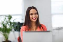 Mujer africana feliz con el ordenador portátil en la oficina imagenes de archivo