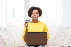 Mujer africana feliz con el ordenador portátil y la tarjeta de crédito Fotografía de archivo