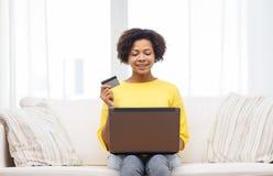 Mujer africana feliz con el ordenador portátil y la tarjeta de crédito Imagen de archivo libre de regalías