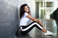 Mujer africana feliz con el peinado rizado negro que se sienta en piso urbano imagenes de archivo