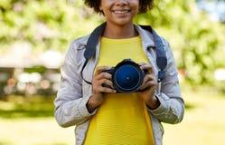 Mujer africana feliz con la cámara digital en parque Imagen de archivo libre de regalías