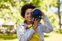 Mujer africana feliz con la cámara digital en parque Fotografía de archivo