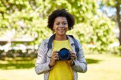 Mujer africana feliz con la cámara digital en parque Fotografía de archivo libre de regalías