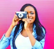 Mujer africana feliz con la cámara vieja del vintage sobre rosa Fotografía de archivo