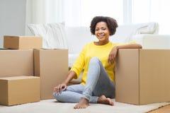 Mujer africana feliz con las cajas de cartón en casa foto de archivo