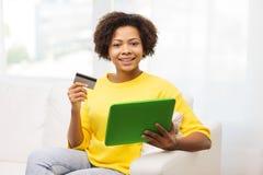 Mujer africana feliz con PC de la tableta y la tarjeta de crédito Foto de archivo