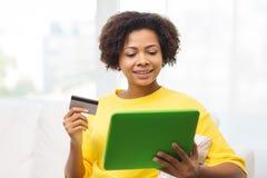 Mujer africana feliz con PC de la tableta y la tarjeta de crédito Imágenes de archivo libres de regalías