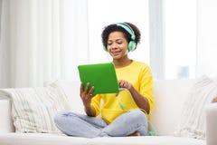 Mujer africana feliz con PC y los auriculares de la tableta Imagen de archivo