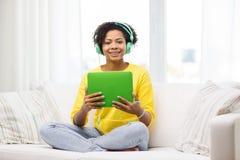 Mujer africana feliz con PC y los auriculares de la tableta Foto de archivo