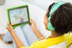 Mujer africana feliz con PC y los auriculares de la tableta Imagenes de archivo