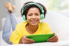 Mujer africana feliz con PC y los auriculares de la tableta Imagen de archivo libre de regalías