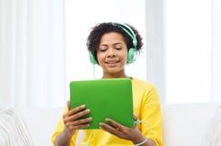 Mujer africana feliz con PC y los auriculares de la tableta Fotografía de archivo libre de regalías