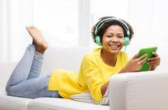 Mujer africana feliz con PC y los auriculares de la tableta Foto de archivo libre de regalías