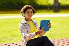 Mujer africana feliz con PC y los auriculares de la tableta Fotos de archivo libres de regalías