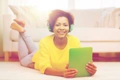 Mujer africana feliz con PC y los auriculares de la tableta Fotografía de archivo